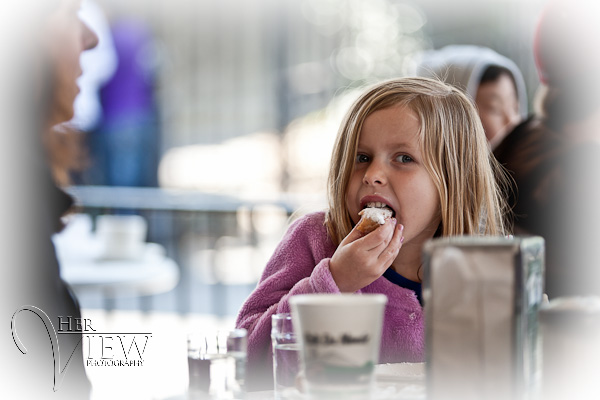 girl eating beignets